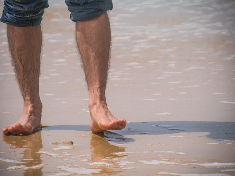 海岸を歩く半ズボンの男性
