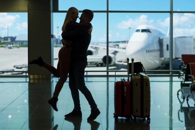 空港でハグをするカップル